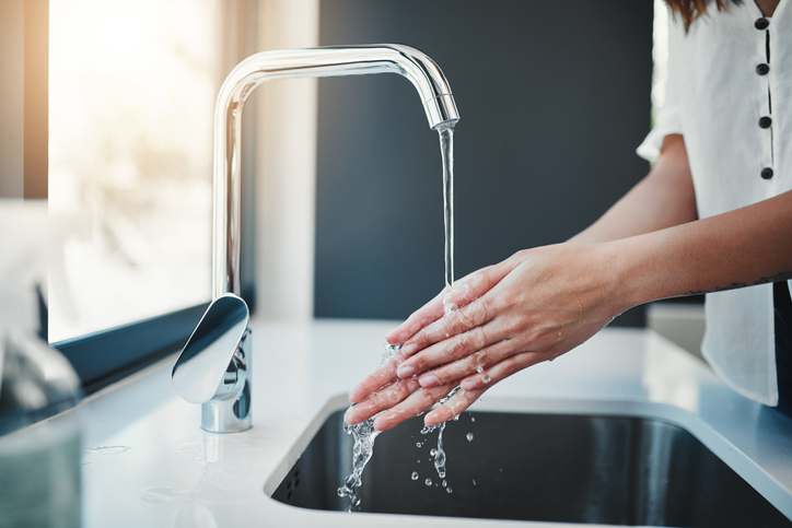 washing hands under modern faucet